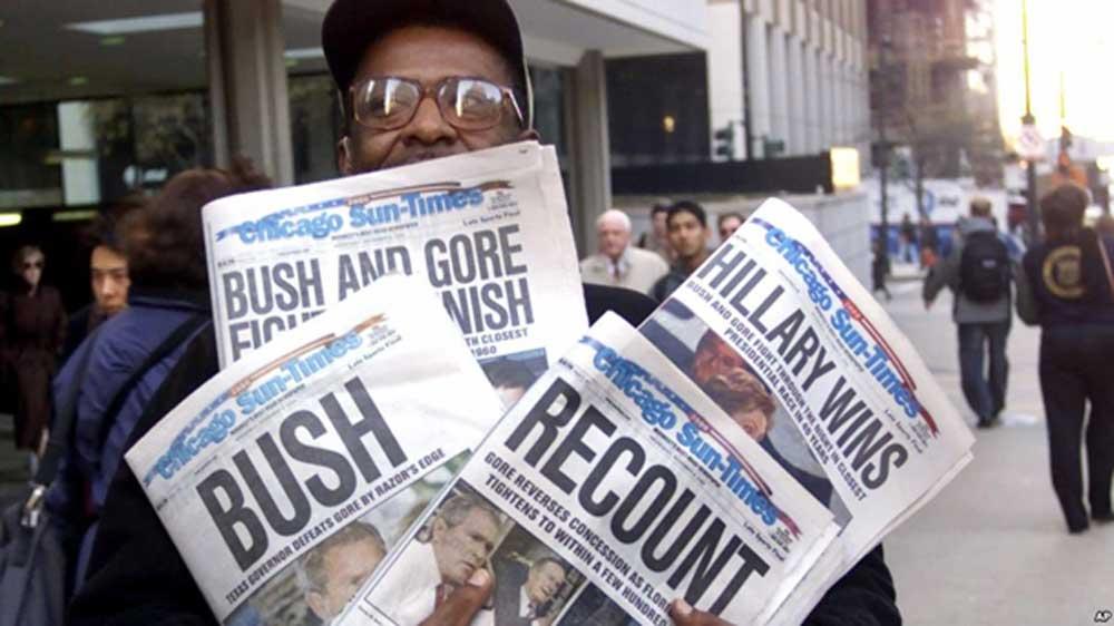 Foto del 8 de noviembre de 2000 en donde Willie Smith muestra cuatro copias del Chicago Sun-Times, cada una con cuatro titulares diferentes que van desde recuento hasta anunciar el triunfo de Bush y e de Al Gore.